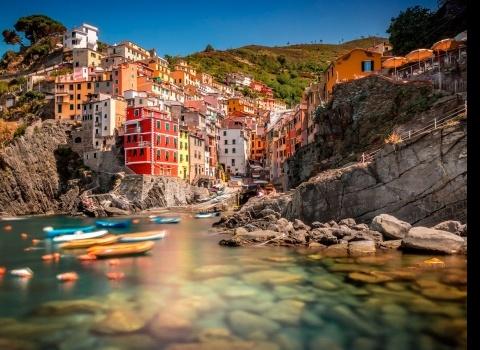 Риомаджоре, Чинкуэ Терре,Италия.Чинкуэ Терре — это пять горных деревень, расположенных на скалах на Лигурийском побережье Италии. Отвесные скалы темного моря контрастируют с цветами домов, которые расположены над скалами. Риомаджиоре привлекают внимание цветными зданиями, опускающимися в море. Здания относятся к XIII веку. Основным элементом красивого вида являются террасовые виноградники.