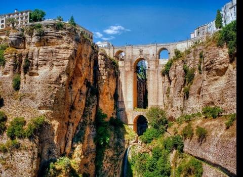 Ронда —это самый прекрасный город в Андалусии, в провинции Малага, расположенный в горном районе, на высокой скале. Город делится на две части рекой Гуадалевин глубокого ущелья Эль Тахо. Объединяют его красивые, массивные мосты XVI века в форме дуги, а также высотой в сто метров Пуэнте Нуэво (произведение 1973 года знаменитого архитектора Мартин-де-Альдеуэла). По обеим сторонам Ронда дома стоят прямо над пропастью.